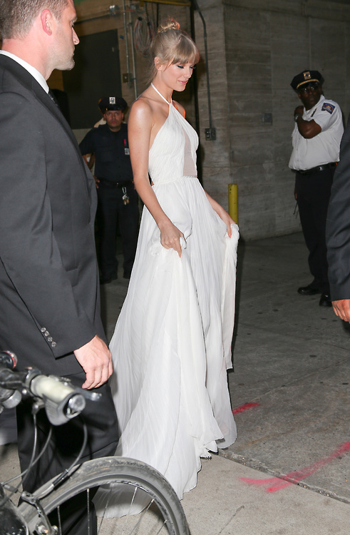 Taylor Swift wearing a white halter neck gown seen leaving the Lincoln Center after attending The Fragrance Foundation Awards in New York City